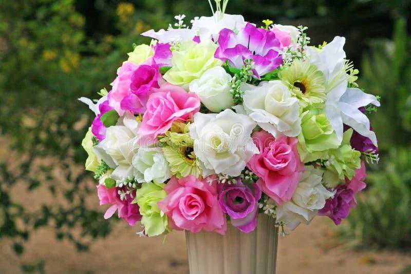 在白色花瓶的人为多彩多姿的花 免版税库存照片