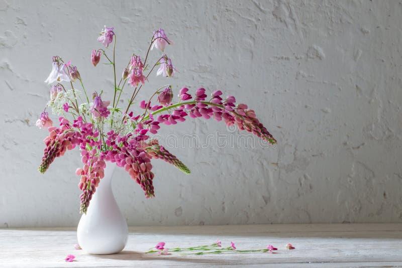 在白色花瓶的桃红色花在白色老背景 库存照片
