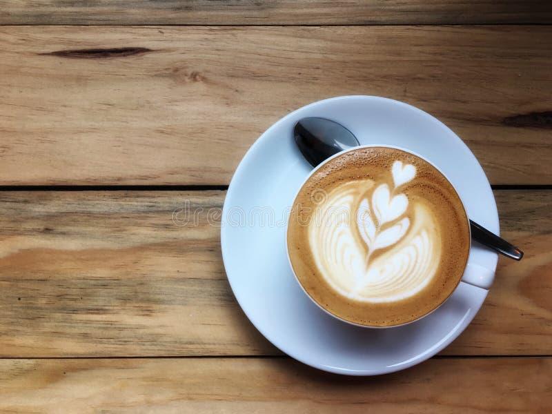 在白色茶杯的热的热奶咖啡咖啡有在木桌背景的匙子的 画象白色心脏的牛奶泡沫艺术  库存照片