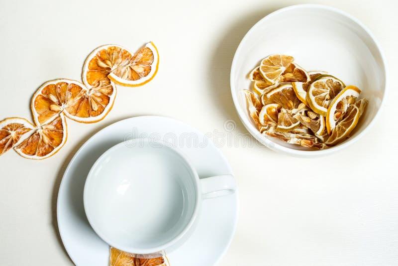 在白色茶碟的空的白色杯子用在边的干柠檬 免版税图库摄影