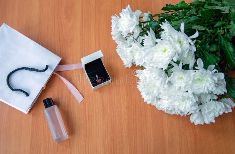 在白色菊花箱子、香水和花的装饰在美丽的花束的 图库摄影
