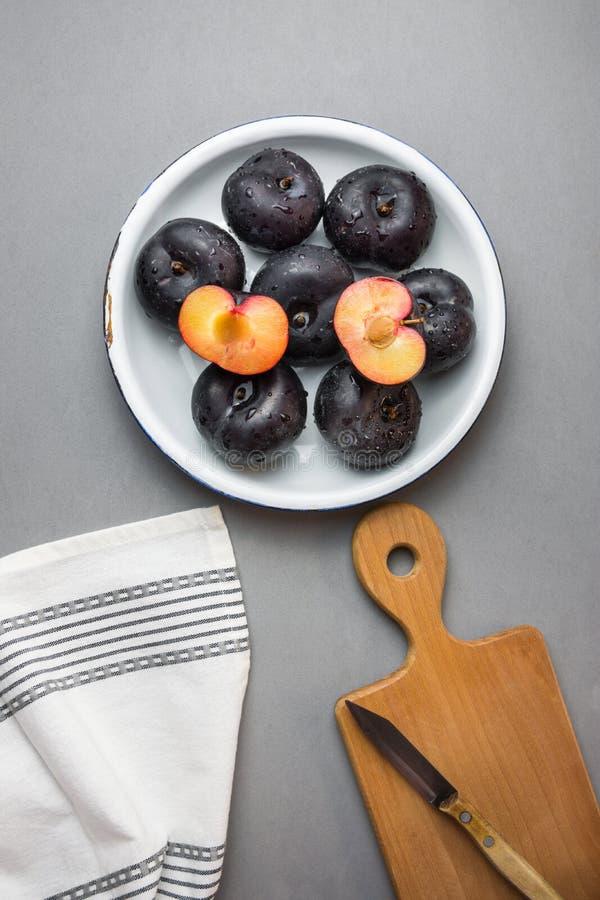 在白色葡萄酒搪瓷板材整个和对分的深红大李子 木在灰色石头的切板刀子白色棉花毛巾 免版税库存照片