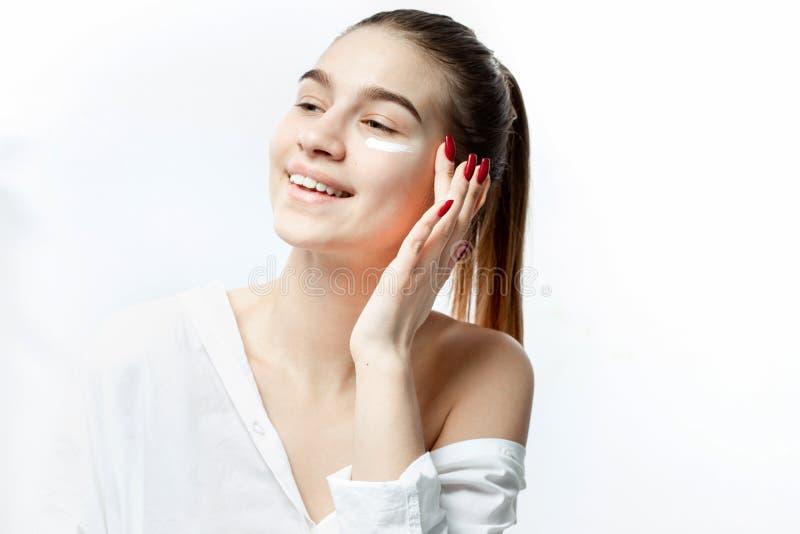 在白色衣裳没有构成的微笑的年轻棕色毛发的女孩打扮的在她的在白色背景的面孔上把奶油放 免版税库存照片