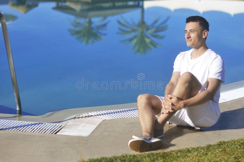 在白色衣裳的年轻人微笑,摆在水池beackground棕榈附近 人烧,放松,休息,旅行 晒日光浴 库存照片