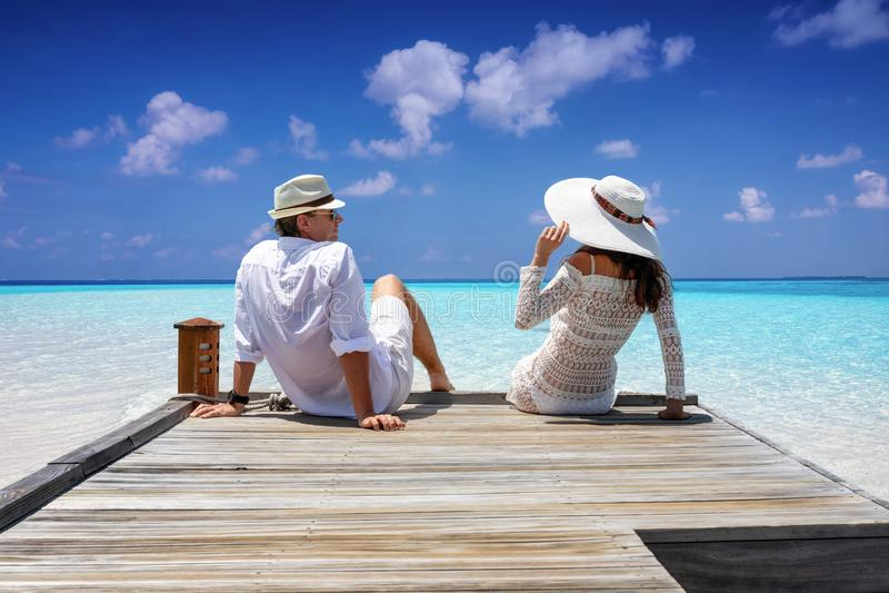 在白色衣裳的旅客夫妇坐一只木跳船 免版税库存图片