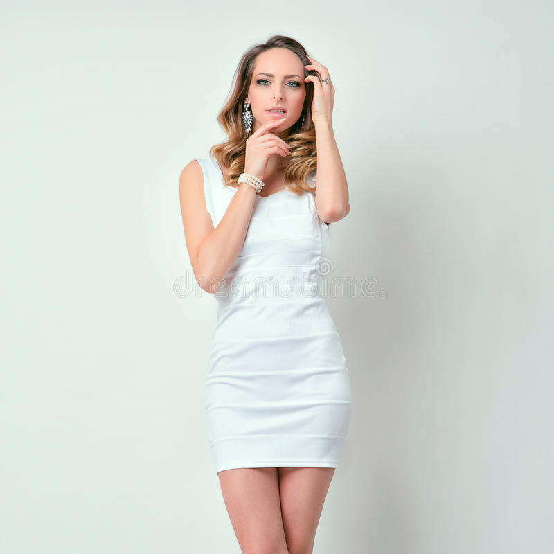 在白色衣裳的有吸引力的深色的女孩姿势 图库摄影