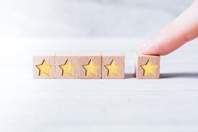 在白色表上的一个男性手指形成由木块和安排的五星等级 库存照片