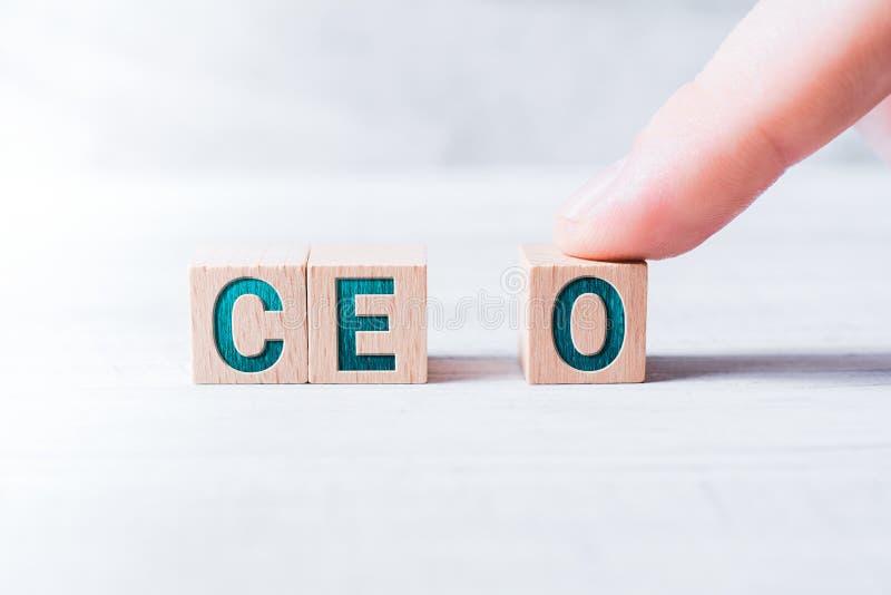 在白色表上的一个男性手指形成由木块和安排的简称CEO 库存图片