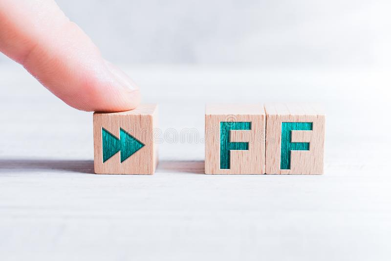 在白色表上的一个男性手指FF形成由木块和安排的简称 免版税库存照片