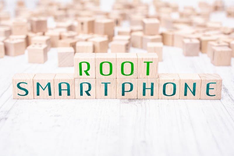 在白色表上的木块形成的词根智能手机 免版税库存照片