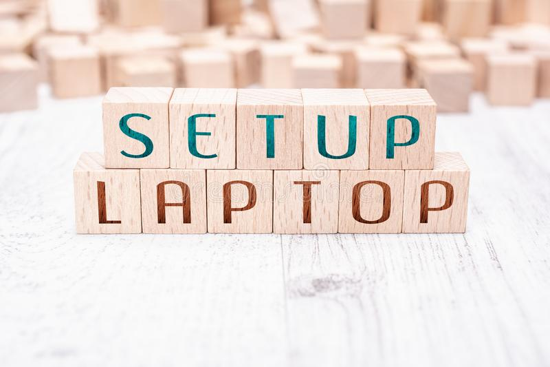在白色表上的木块形成的词设定膝上型计算机 免版税库存照片