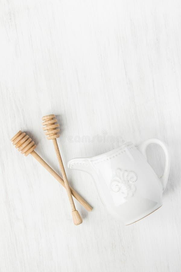 在白色表上的葡萄酒陶瓷奶油色牛奶罐木蜂蜜浸染工匙子 烹调车间海报的假日烘烤 免版税库存照片