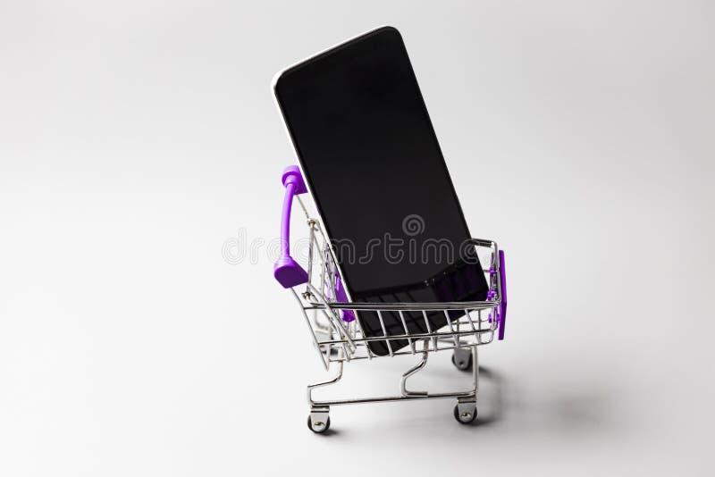 在白色表面上,在迷你购物车中观看智能手机 库存图片