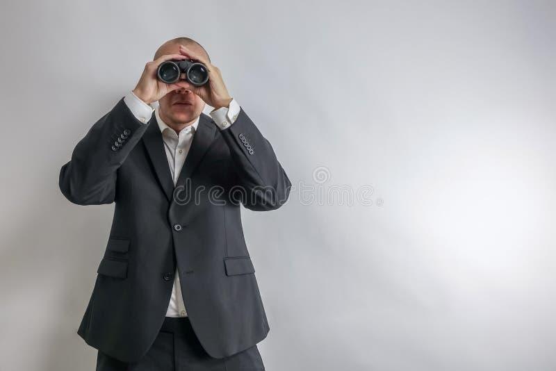 在白色衬衣和黑衣服的商人在双筒望远镜侦察 免版税库存照片