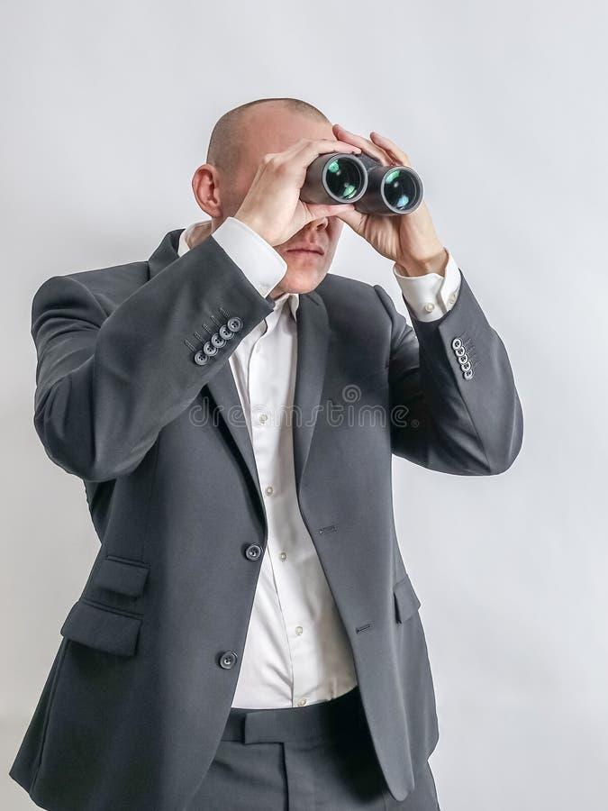 在白色衬衣和黑衣服的商人在双筒望远镜侦察 库存照片