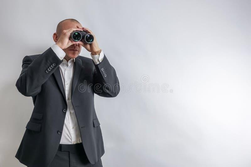 在白色衬衣和黑衣服的商人在双筒望远镜侦察 免版税库存图片