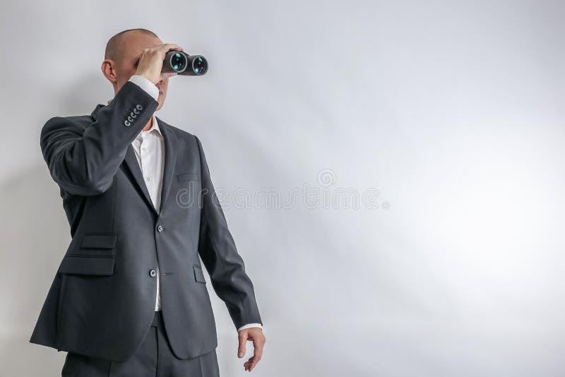 在白色衬衣和黑衣服的商人在双筒望远镜侦察 库存图片