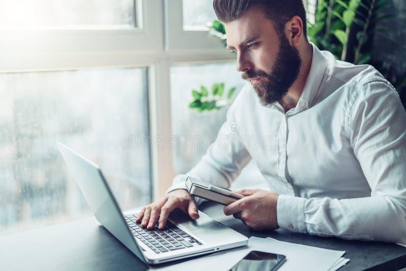 在白色衬衣的年轻有胡子的商人坐在桌上并且研究膝上型计算机 自由职业者在家工作 学生 图库摄影
