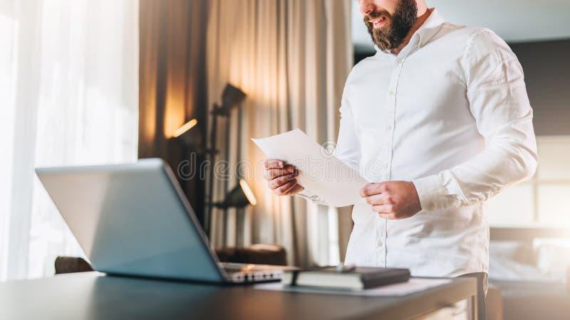 在白色衬衣的年轻有胡子的商人是在膝上型计算机,读书文件前面的常设近的书桌 自由职业者工作 免版税库存图片