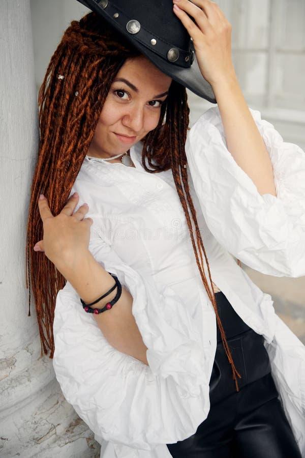 在白色衬衫、黑皮革帽子和长裤打扮的Dreadlocks时兴的女孩,摆在老宫殿字体  免版税库存照片
