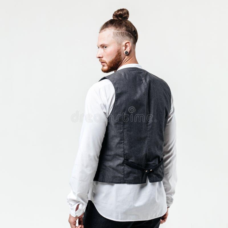 在白色衬衫和灰色长裤姿势的在灰色背心有胡子和小圆面包发型打扮的英俊的时髦的人在 免版税库存照片