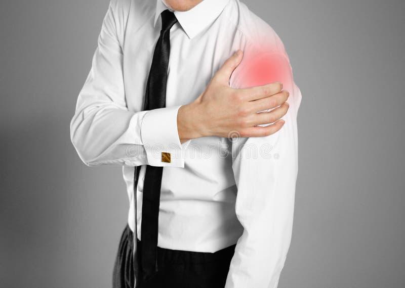 在白色衬衫和领带藏品手的商人 使肩膀痛苦 库存照片