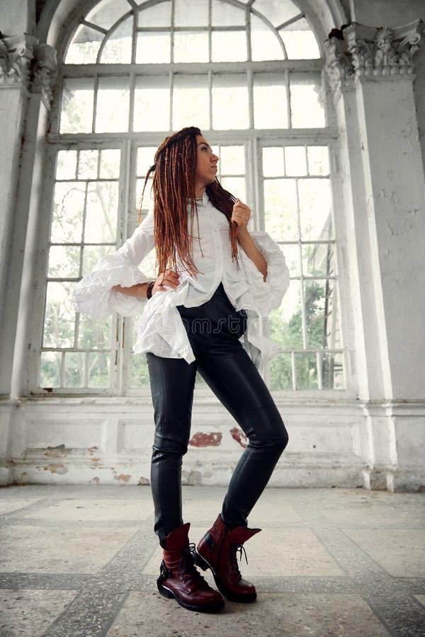 在白色衬衫和黑皮革长裤打扮的Dreadlocks时兴的女孩摆在老大窗口字体  免版税库存图片