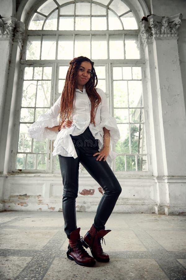 在白色衬衫和黑皮革长裤打扮的Dreadlocks时兴的女孩摆在老大窗口字体  图库摄影