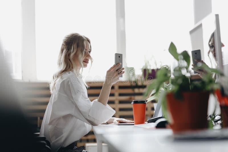 在白色衬衫打扮的年轻美女与坐在有一台膝上型计算机的书桌的电话一起使用在一轻现代 库存照片