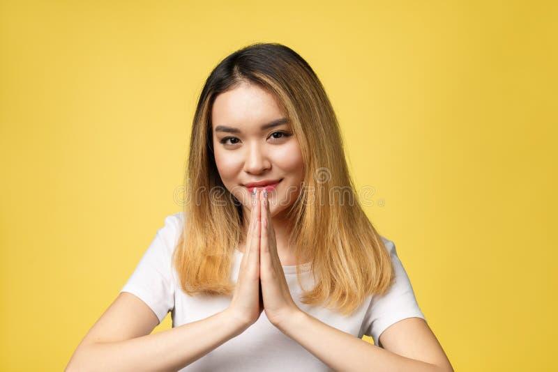 在白色衬衫的Tan皮肤女性模型 秀丽时尚神色样式在演播室照明设备的黄色背景中,你好sawadee 图库摄影
