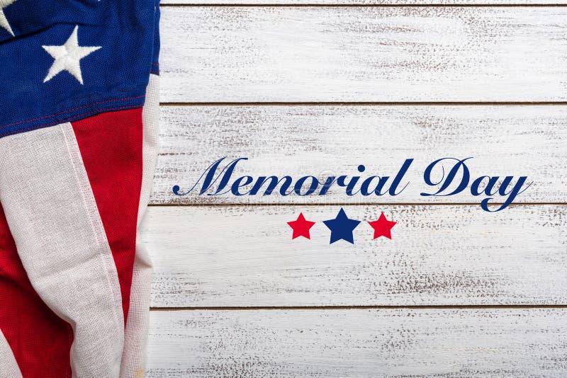 在白色被佩带的木背景的美国国旗与阵亡将士纪念日问候 免版税库存图片