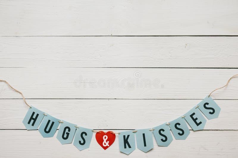 在白色谷仓木板条背景的拥抱和亲吻横幅诗歌选好的题字 重点纸红色 拷贝的,文本空间, 免版税库存图片