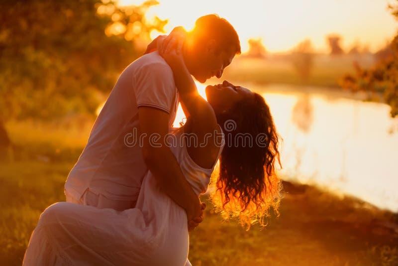 在白色跳舞的年轻夫妇在日落背景  免版税图库摄影