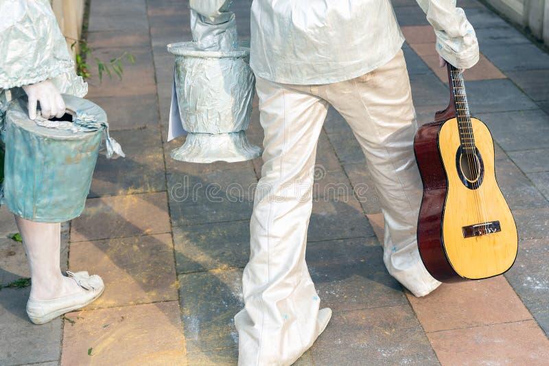 在白色银色油漆街道艺术家绘的对走在城市公园 有吉他的居住的雕象执行者 图库摄影