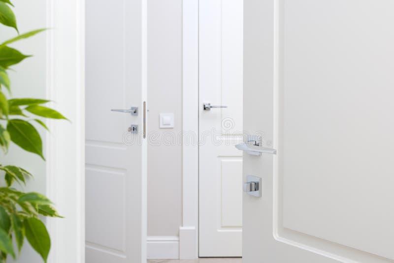 在白色门的现代镀铬物门把手 美好的特写镜头内部 免版税库存图片