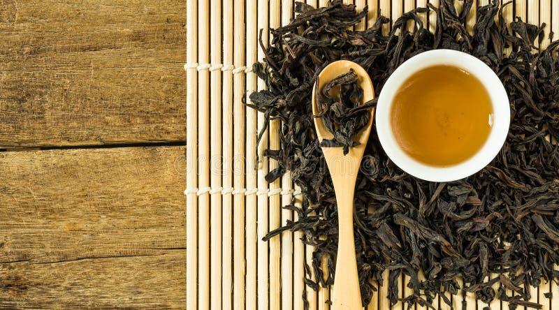 在白色陶瓷杯子和干茶叶的中国茶在木匙子 库存照片