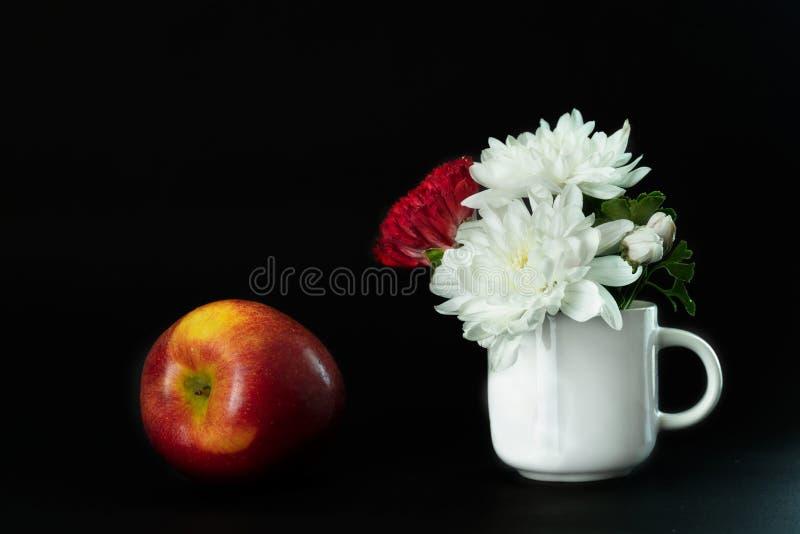 在白色陶瓷杯子和苹果果子的红色白花在黑背景的食物洛可可式经典静物画样式的 免版税库存照片