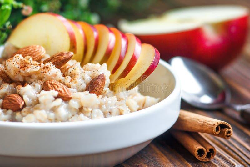 在白色陶瓷碗的有机燕麦粥粥有苹果、杏仁、蜂蜜和桂香健康早餐的 免版税图库摄影