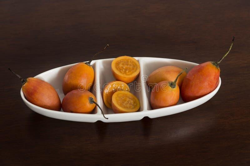 在白色陶瓷碗的树蕃茄在木背景 图库摄影