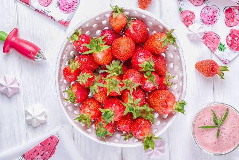 在白色陶瓷碗的草莓和桃红色草莓奶昔或者鸡尾酒 库存照片