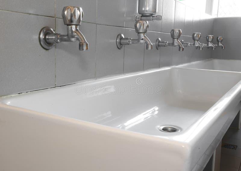 在白色陶瓷水槽的钢轻拍 免版税库存照片