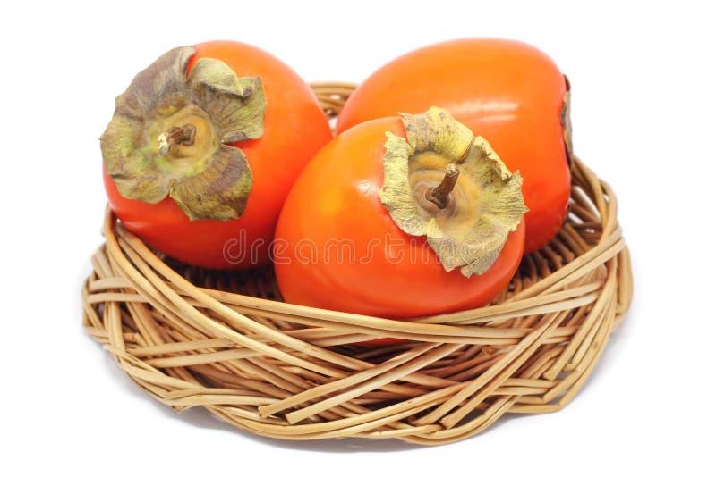 在白色隔绝的一个柳条碗的三个柿子 库存照片