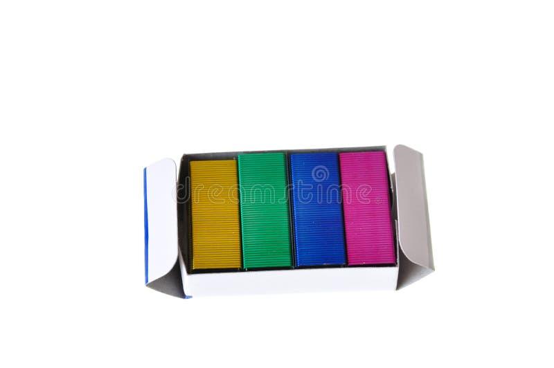 在白色隔绝的一个箱子五颜六色的钉书针 库存图片