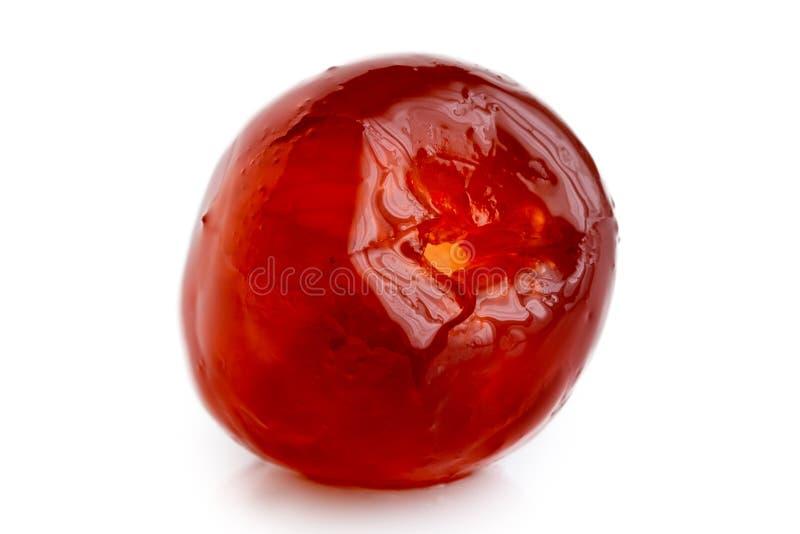 在白色隔绝的一棵唯一红色糖渍的樱桃的特写镜头 库存照片