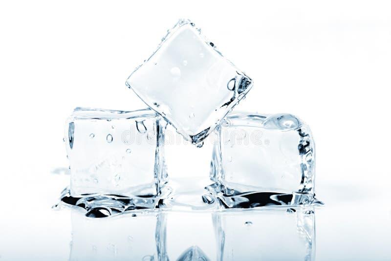 在白色隔绝的三个冰块熔化 免版税库存图片