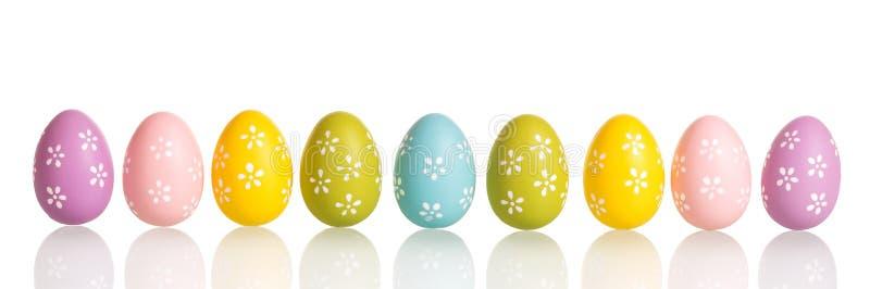 在白色隔绝的五颜六色的复活节彩蛋行  免版税库存照片