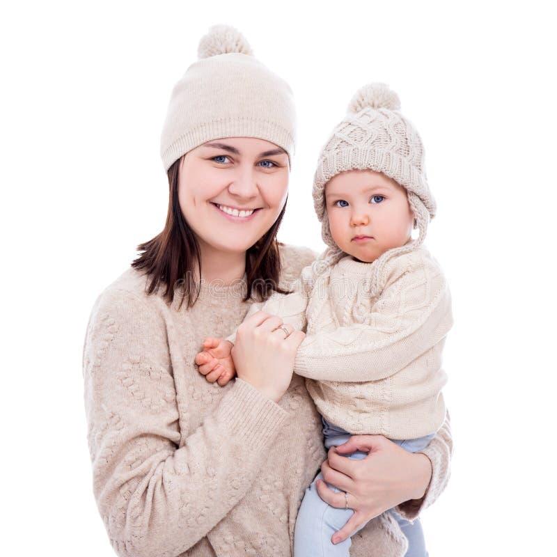 在白色隔绝的冬季衣服的年轻母亲和可爱宝贝女孩 免版税库存图片