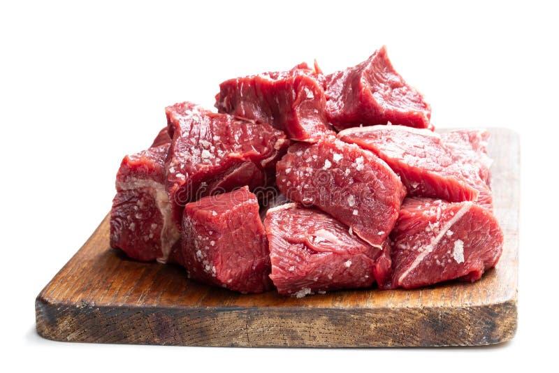 在白色隔绝的切板的切的未加工的牛肉 库存图片