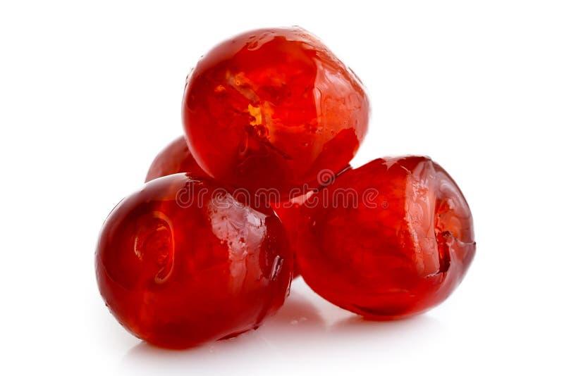 在白色隔绝的四棵红色糖渍的樱桃特写镜头  免版税库存图片