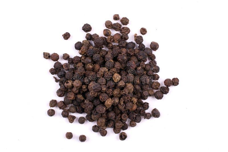 在白色隔绝的堆干燥黑胡椒种子 库存照片